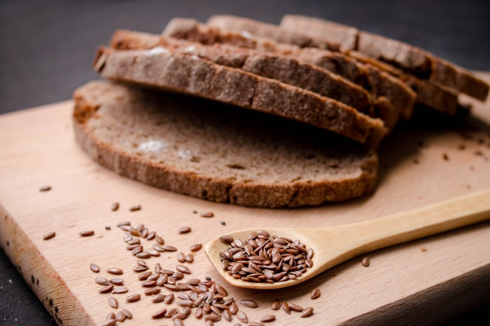 Slices of  dark  fresh bread with  seeds on dark wooden backgrou